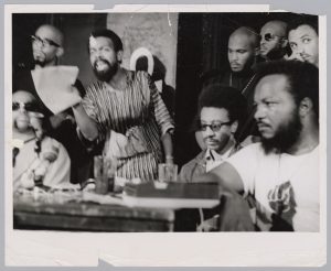 A bandaged Amiri Baraka (LeRoi Jones) holds a press conference inside the Spirit House in Newark during the National Conference on Black Power. Baraka was wounded after being arrested on gun charges and beaten by Newark Police during the 1967 rebellion. Left of Baraka is cultural nationalist leader Ron Karenga (US Organization). Right of Baraka is H. Rap Brown, Chairman of the Student Nonviolent Coordinating Committee (SNCC). -- Credit: Amiri Baraka Papers; Rare Book and Manuscript Library, Columbia University Library