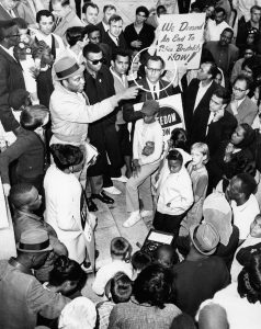 Photograph of a rally held by the Newark branch of the Congress of Racial Equality (CORE) to protest the killing of Lester Long by Newark policeman Henry Martinez. The shooting of Lester Long was one of the most well-known and contentious cases of alleged police brutality in Newark during the 1960s and reinvigorated community demands for a police review board. -- Credit: Photo by Jim Lowney, Doug Eldrige Collection