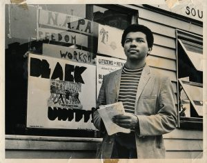 """Photo of Junius Williams, member of the United Brothers, standing in front of NAPA headquarters. On the window behind him is a poster for the United Brothers that reads """"Black Unity! Self-Government is Possible in 1970. Let's Do It Together!"""""""