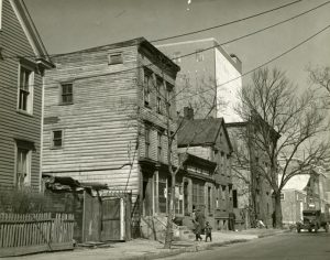 "Sidewalk view of ""slum"" housing in Newark. Housing discrimination in the city segregated Newark's Black communities to areas where this type of housing predominated. -- Credit: WPA Photographs, New Jersey State Archives"