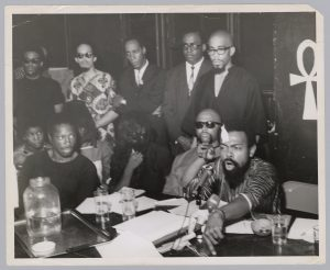 A bandaged Amiri Baraka (LeRoi Jones) holds a press conference inside the Spirit House in Newark during the National Conference on Black Power. Baraka was wounded after being arrested on gun charges and beaten by Newark Police during the 1967 rebellion. To the left of Baraka are cultural nationalist leader Ron Karenga (US Organization) and the mother of James Rutledge (veiled), who was shot 39 times by State Police during the rebellion.