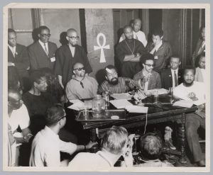 A view inside a press conference held at Amiri Baraka's Spirit House in Newark during the National Conference on Black Power in July, 1967. Seen seated in the photo from L-R are: the mother of James Rutledge (shot 39 times during the rebellion), Ron Karenga (US Organization), Amiri Baraka (United Brothers and CFUN), H. Rap Brown (SNCC), and Floyd McKissick (CORE). Newark Community Union Project (NCUP) and SNCC member Phil Hutchings can also be seen standing behind Brown and McKissick. -- Credit: Amiri Baraka Papers; Rare Book and Manuscript Library, Columbia University Library