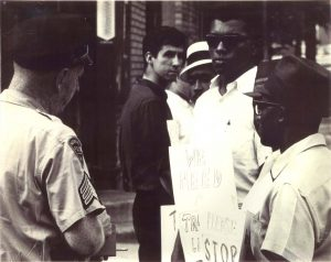 Photograph of members of the Newark Community Union Project (NCUP) at a 1965 demonstration for a traffic light at Avon and Badger Avenues. Tom Hayden is pictured in the center of the photo, along with Junius Williams (sunglasses and sign). --Credit: Junius Williams Collection