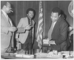 Donald Tucker, Junius Williams, and Ken Gibson chat in the Mayor's office in the early 1970s. --Credit: Newark Public Library