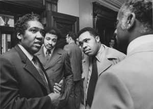 George Richardson (left) chats with Essex County Democratic Assemblymen and Mayor Ken Gibson (second from right) outside the assembly chambers in 1972. --Credit: Newark Public Library