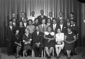 Photo of Earl Harris (front row, third from left) with a group of political and community leaders, possibly a civic association, taken by Newark photographer Al Henderson. --Credit: Newark Public Library