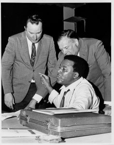Jesse Allen, acting chairman of the UCC, speaks at a meeting held to nominate community members for positions in the organization. Standing behind him are Michael Duffy, acting director of the UCC, and Sidney Reitman, UCC counsel. -Credit: Newark Public Library
