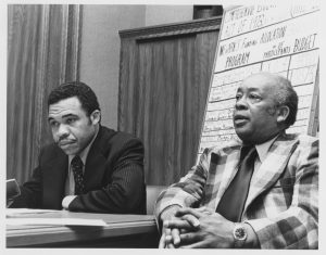 Harry Wheeler (right) speaks at a meeting while Mayor Ken Gibson (left) listens in. Under the Gibson administration, Wheeler was appointed Director of Manpower, a job training program, and often served as the Mayor's representative at speaking events. --Credit: Roberta Pfeifer/Newark Public Library