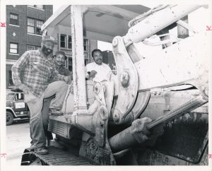 Mayor Gibson poses for a photo on a bulldozer with construction workers. --Credit: Newark Public Library