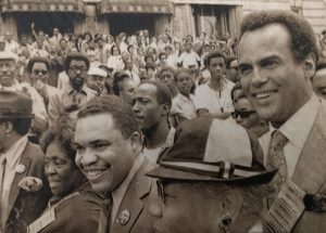 Mrs. Fannie Lou Hamer (left), Ken Gibson (center), and Harry Belafonte (right), march side-by-side down Broad Street on June 15, 1970, to promote Gibson's mayoral campaign. Gibson won the run-off election the next day, becoming Newark's first African American Mayor. --Credit: UPI Telephoto