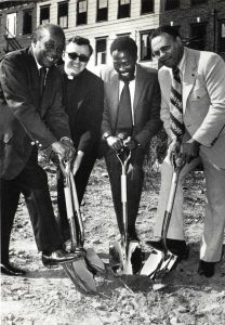 A 1975 groundbreaking ceremony of the New Community Corporation (NCC), an economic and housing development corporation founded in 1968 by Rev. William Linder. (L-R) George Wheeler (representative of Mayor Ken Gibson), Rev. Linder, Willie Wright (President of NCC), and William Blakely (Engelhard Industries). -- Credit: D.J. Zehnder/John T. Cunningham