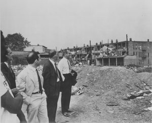 Willie Wright (left) leads a group of Newark businessmen on a tour of the city's Central Ward in 1968. Wright, head of the United Afro-American Association, led tours of the Central Ward to demonstrate the conditions faced by its predominantly Black residents, and to promote investment in the area. -- Credit: Newark Public Library