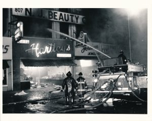 Members of the Newark Fire Department work to put out a fire at the Hartley's store at Broad Street and Branford Place on July 14, 1967. -- Credit: The Star-Ledger