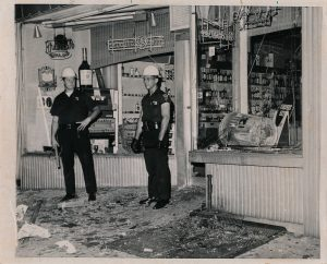 """""""Newark, NJ: Policemen stand beside the broken window of a liquor store on Belmont Avenue after outbreak of violence in Newark early July 13th. Negroes enraged by the alleged beating of a cab driver by police besieged a station house and touched off a wave of window-smashing and looting. Trash can (right) was used to break this store window."""" -- Credit: UPI Photo"""