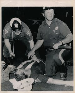 """Newark, NJ: Injured patrolman Joseph Strumule lies on the ground and receives aid from two unidentified fellow patrolmen after being struck by a stone on Springfield Avenue here during early morning disorders July 14th."" -- Credit: UPI Telephoto/Newark Public Library"